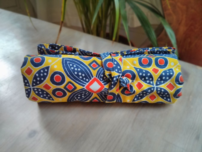 Pencil roll in yellow, red and blue repeat print, rolled up tightly and tied around its middle.